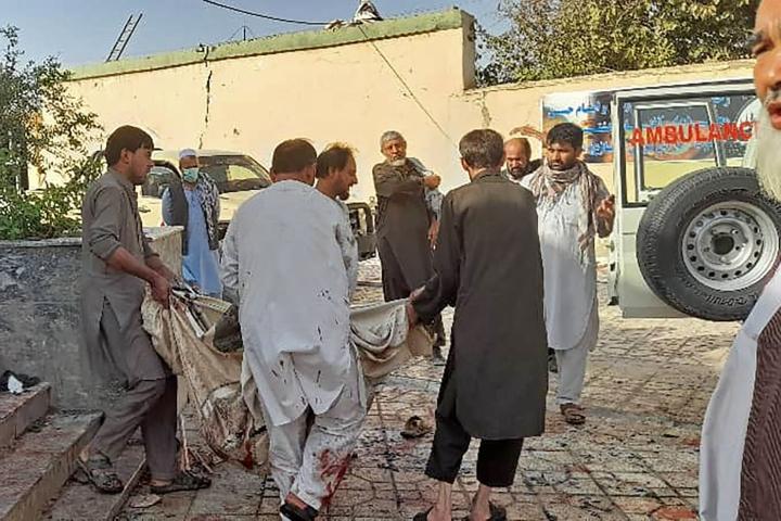 Pommi-iskun uhria viedään pois tapahtumapaikalta Kunduzissa perjantaina.  LEHTIKUVA / AFP