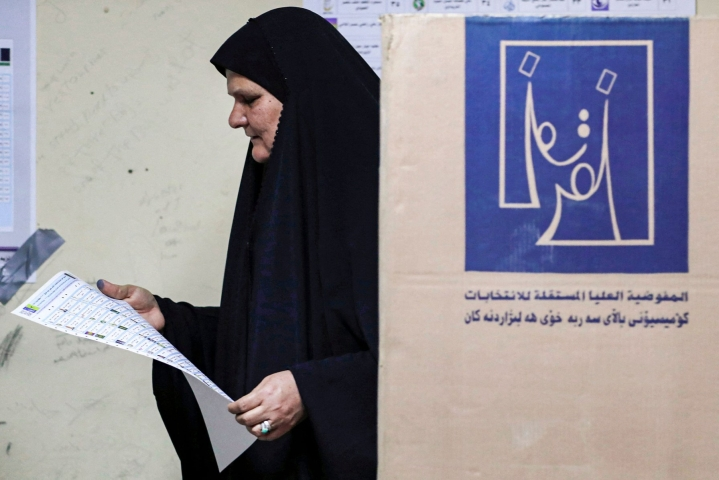 Vaalilautakunnan mukaan vaaliuurnilla kävi nyt runsaat yhdeksän miljoonaa irakilaista. Nainen tutki äänestyslippua sunnuntaina Bagdadissa. LEHTIKUVA / AFP