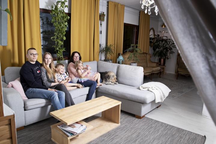 Olohuoneen toinen puoli on vaaleammissa sävyissä. Joonas Keijonen, Reeta Keijonen, Eino Keijonen, Kristiina Koponen ja Judith Keijonen sekä Napu mahtuvat kaikki sohvalle katsomaan televisiota.