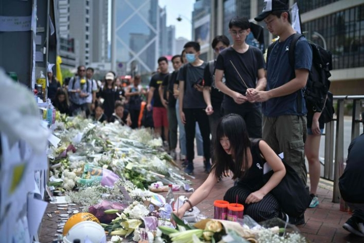 Hongkongissa mielenosoitusten johtajat ovat kehottaneet protestoijia tuomaan valkoisia kukkia paikalle, jonne mies putosi kuolemaansa.  LEHTIKUVA/AFP