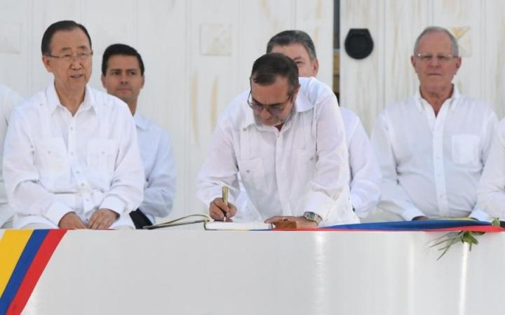 Farc-sissien johtaja Timoleon Jimenez allekirjoittamassa Kolumbian historiallista rauhansopimusta. Vasemmalla YK:n pääsihteeri Ban Ki-moon. LEHTIKUVA/AFP