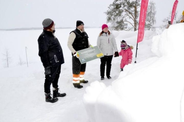 Juha Käkelä luovutti 1?700 euron lahjoituksen ENO-verkkokoululle ILO!LUMI-tapahtumassa, vastaanottajana Kaija Sarasmäki tyttärensä Hilman kanssa. Vasemmalla Timo Reko Maaseudun sivistysliitosta.