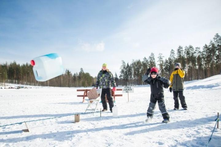 Eeli Ikonen, 5, heittää lumicurlingkanisteria, Aleksanteri Sippola, 10, ja Honkalammen nuorisoseuran Jaan Tarkkonen seuraavat.