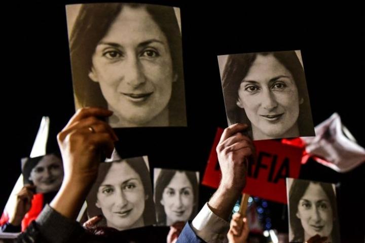 """Marraskuussa 2019 ihmiset osoittivat mieltään Maltan pääministerin virkahuoneiston edustalla, heidän kylteissään oli tapetun journalistin kuvia sekä tekstejä kuten """"mafiahallitus"""". LEHTIKUVA / AFP / STRINGER"""