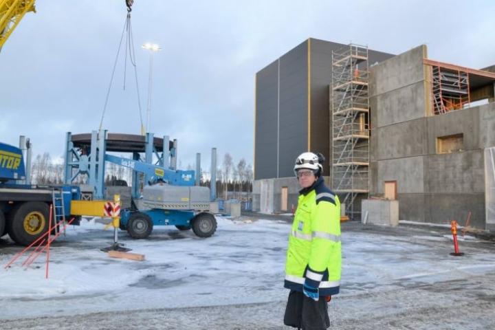 Työmaapäällikkö Kyösti Schwartz esittelee hiilitehtaan työmaata. Pyöreä sininen metallikehikko on 30-metriseksi nousevan uunin rakenteita, oikealla on jälkikäsittelytilat sekä sähkö- ja automaatiotilat. Laitoksen koekäytön on määrä alkaa ensi syksynä.