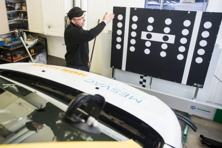 Esa Tolvanen esittelee tuulilasikameran kalibrointiin tarkoitettua taulua. Eri automerkeille on omat taulunsa. Tämä taulu on tarkoitettu Volkswagenin tuulilasikameroiden kalibrointiin.