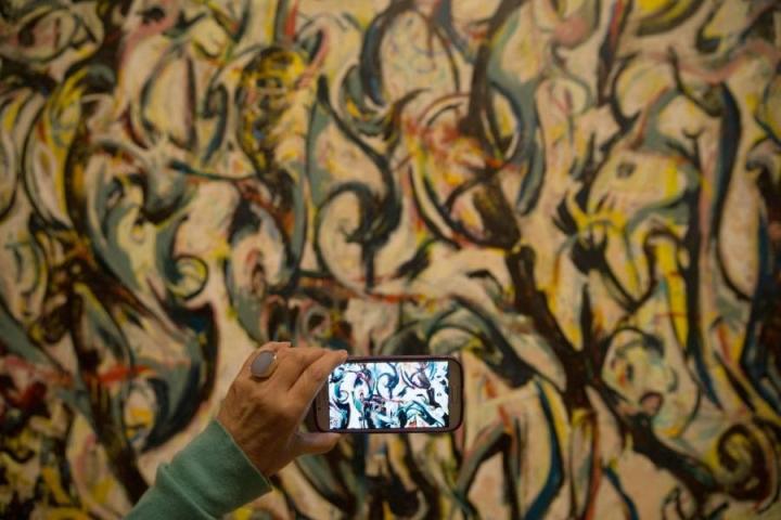 Museovierailija otti kuvia Jackson Pollockin maalauksesta Lontooossa viime viikolla. LEHTIKUVA/AFP