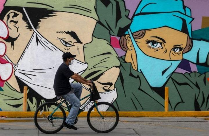 Mies pyöräili koronamuraalin ohi Meksikossa. Johns Hopkinsin yliopiston mukaan koko maailmassa on kirjattu yhteensä jo lähes puoli miljoonaa koronaan liittyvää kuolemaa. Worldometer-tilastosivuston mukaan 500000 kuolemantapauksen rajapyykki olisi jo ylitetty.