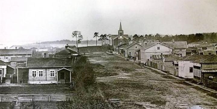 Talvella kaadettu mänty oli yksi entisen kirkon vieressä kasvaneista puista, jotka ovat kuvassa kirkon vasemmalla puolella. Kuva on noin vuodelta 1890.
