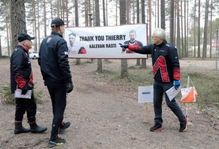 Urpo Väänänen (oik.), Jussi Silvennoinen ja Reino Nevalainen esittelevät kuntorastien ratojen suunnittelijan Thierry Gueorgioun julistetta, joka odottaa kuntorastilaisia maalissa.