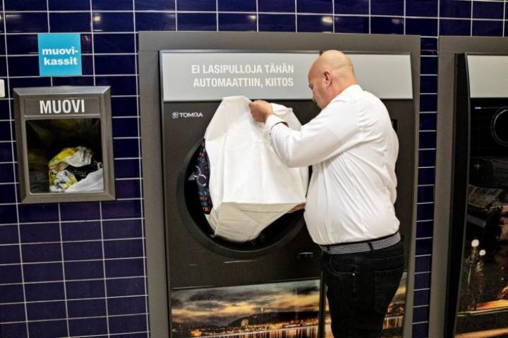 Päivärannan K-Citymarketin kauppias Pasi Toppari näyttää, miten uuteen automaattiin voi kipata kerrallaan säkillisen tölkkejä ja muovipulloja.