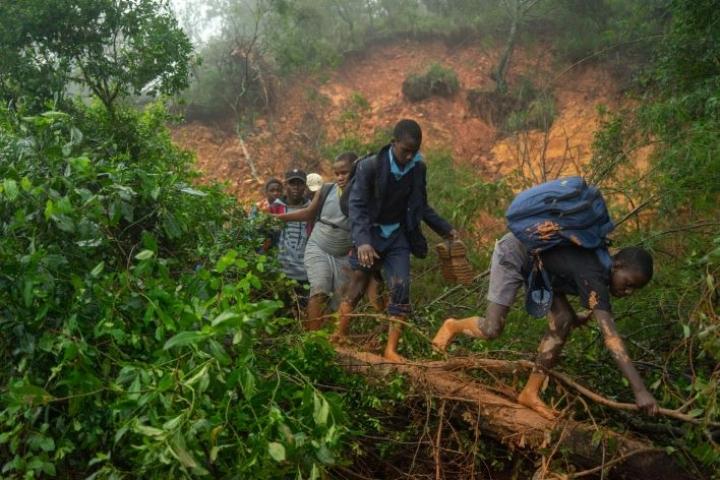 Koululaiset kävelivät myrskyn aiheuttaman mutavyöryn ohi sunnuntaina Mosambikissa. LEHTIKUVA/AFP