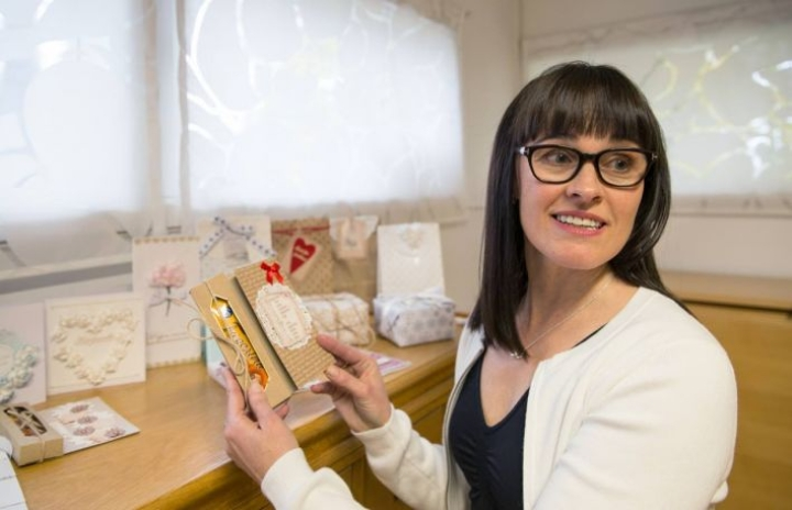 Heli Jussila esittelee rasiakorttipohjaa, johon voi tyylikkäästi sujauttaa vaikkapa suklaapatukan tai tuikkukynttilöitä ystävälle lahjaksi.