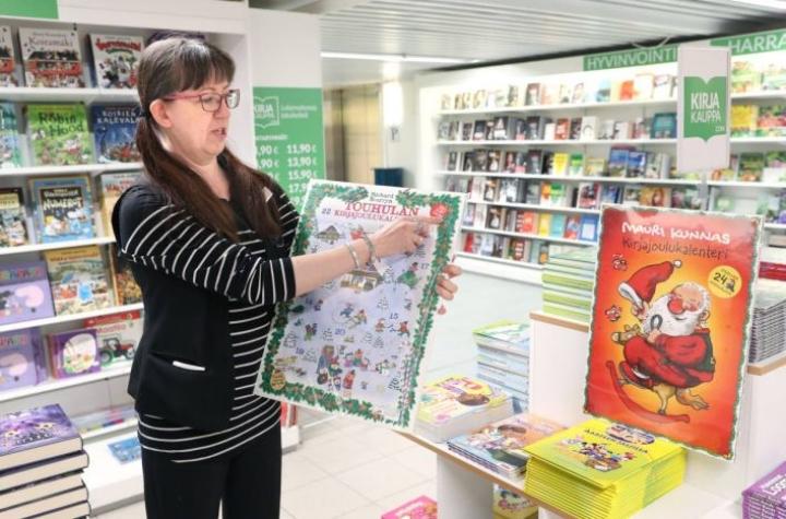 Myyjä Päivi Ärväs ja Sokoksen kirjaosaston minikirjoja sisältävät paksut lukukalenterit Mauri Kunnakselta ja Touhulasta.