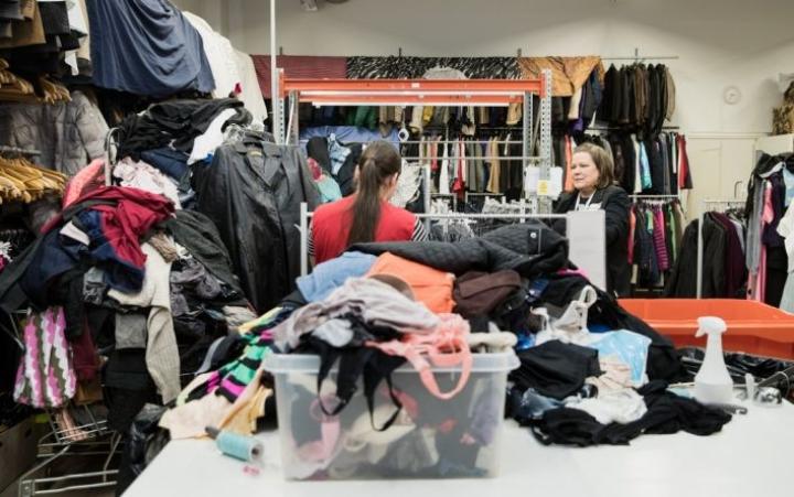 Joensuun Kontti-myymälän työntekijöiden käsille on tarvetta, sillä lahjoituksia on tehty varsinkin kevään jälkeen tavallista enemmän. Raakel Paananen lajittelee ja tarkistaa saapuneita vaatelahjoituksia. Oikealla Kontti-päällikkö Susanna Laaksonen.