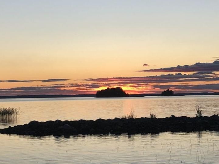 Iltaaurinko laskee horisontin taakse Pyhäselän rannassa 27. elokuuta.