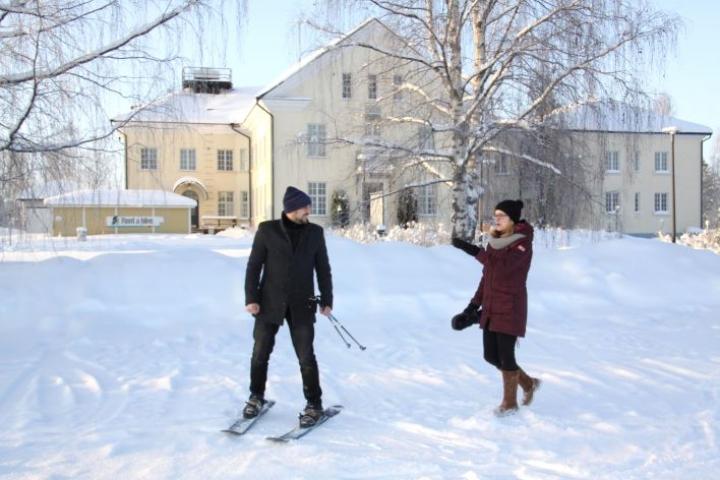 Paalasmaa on tuollapäin, Heta Pulkkinen opastaa Jason Koukkua. Jaloissaan miehellä ovat lumiliukukengät, joita voi vuokrata Hyvärilästä.