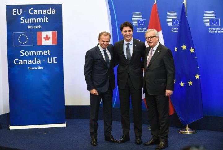 Vapaakauppasopimuksen allekirjoituksen tielle uhkasi tulla vielä uusi mutka, kun Justin Trudeauta (kesk.) kuljettanut kone joutui kääntymään takaisin lentokentälle Kanadassa. LEHTIKUVA/AFP