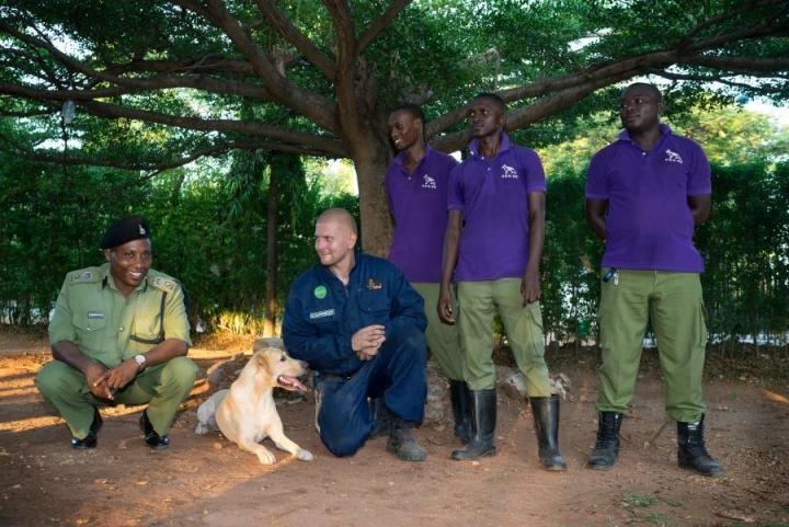 Norsunluukoira Rokka poseeraa Tansanian koirapoliisin päällikön Egyne Emmanuelin (vas.) ja isäntänsä Toni Lahtisen välissä. Rokan seurassa myös koirakouluttajat Peeter, Omary ja Said.