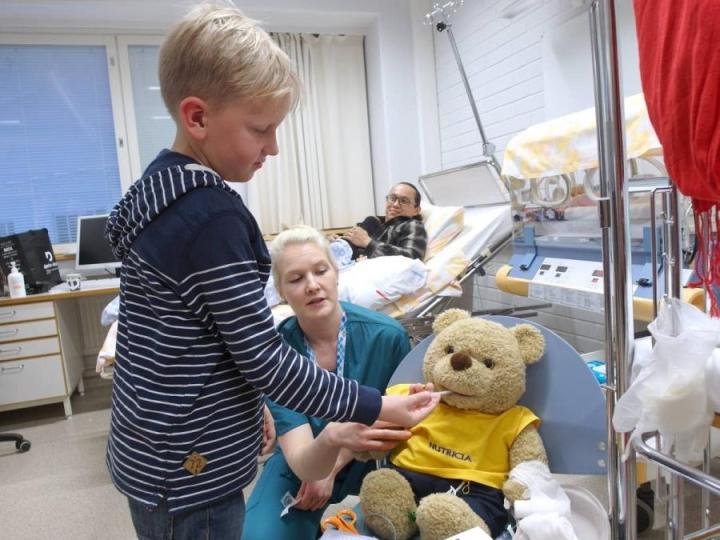 Sairaanhoitaja Jenny Mustonen Loarca opastaa Riku Martikaista hoitamaan nallesairaalan nallea.