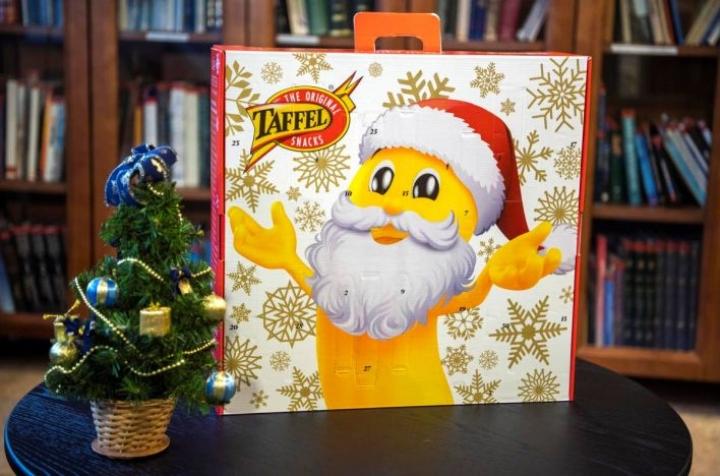 Sipsijoulukalenterissa komeilee joulupukiksi pukeutunut juustonaksu. Pienen matkalaukun kokoisessa kalenterissa on luukkuja molemmin puolin.