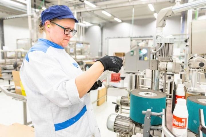 Pakkaaja Piia Puustinen tarkistamassa Diesel 100 -etikettien kiinnitystä.