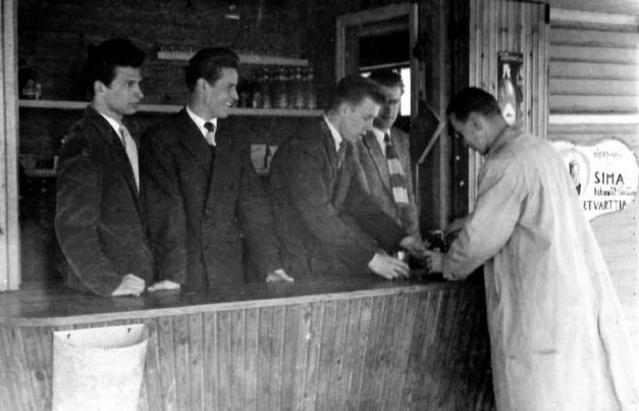 Ilosaaren uimalaitoksen kioski kesällä 1954. Tiskin takana lyseon poikia, vasemmalta Lauri Toivanen, Martti Sihvonen sekä varsinaiset kioskin hoitajat Kyösti Mäkinen ja Jaakko Salonoja. Asiakkaana Karjalaisen toimittaja Paavo Nieminen.