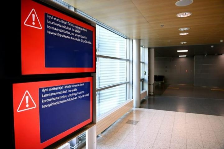 Koronaviruksesta tiedottava kyltti Helsinki-Vantaan lentokentällä. EU-komissio vetoaa kirjeessään, että jäsenmaat linjaisivat sisärajoja koskevia rajoituksiaan lähemmäs EU:n neuvostossa sovittuja suosituksia. LEHTIKUVA / ANTTI AIMO-KOIVISTO