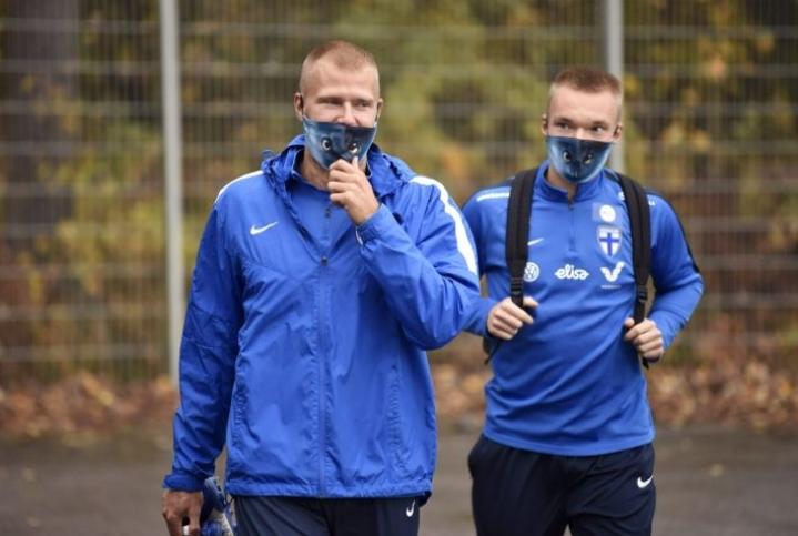 Paulus Arajuuri (vas.) ja Ilmari Niskanen saapuvat Huuhkajien maskeissa miesten jalkapallomaajoukkueen harjoituksiin. LEHTIKUVA / JUSSI NUKARI
